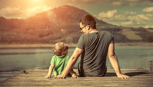 папа с сыном сидят у озера
